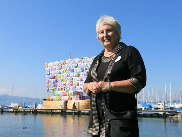 Emilia Kabakov steht vor einem Schiff mit buntem Segel.