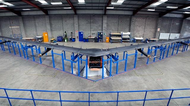 Ein grauer Bumerang, 30 Meter Spannweite, in einer Industriehalle aufgebockt.