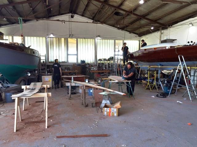 Werft-Halle. Darin stehen zwei Boote. Männer arbeiten mit Holz.
