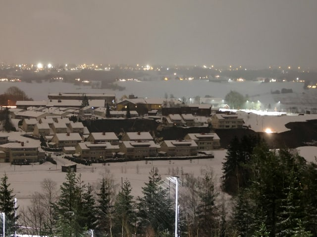 Schneebedecktes Dorf im Dunkeln