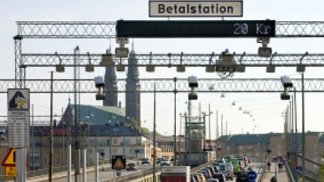 """Eine Strasse in Stockholm, darüber ein Gerüst mit einem Schild mit der Aufschrift: """"Betalstation""""."""