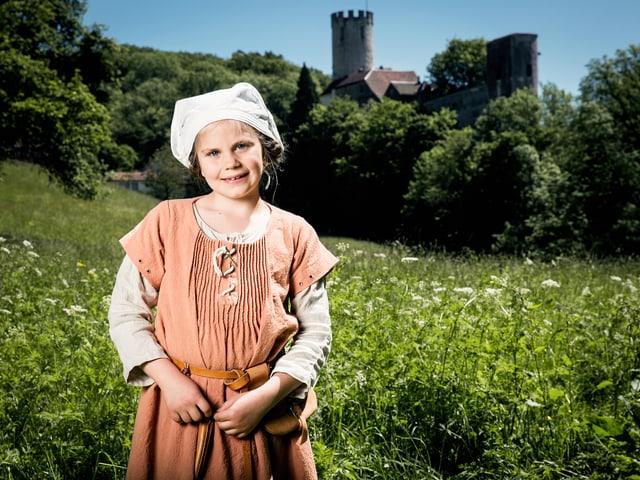 Junges Mädchen in mittelalterlicher Kleidung auf einer Wiese mit einer Burg im Hintergrund