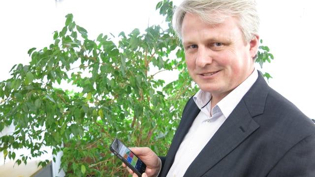 Ein Mann steht vor einer Büropflanze und hält ein Smartphone in der Hand.