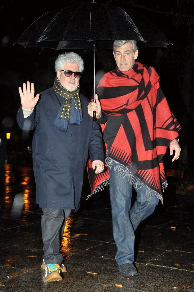 Almodovar und Iglesias auf der Strasse laufend. Es regnet und die beiden stehen unter einem Regenschirm.
