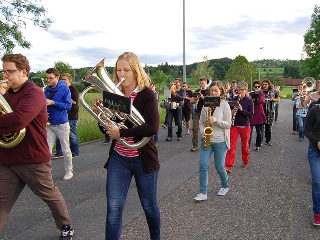 Musikanten marschieren und spielen auf Strasse.