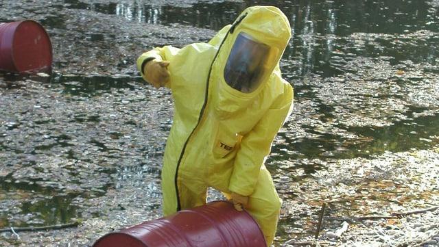 Mann in gelbem Schutzanzug. Rote Fässer.