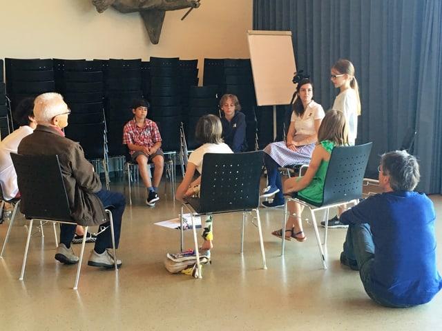 Eine Gruppe von Kindern sitzt auf Stühlen in einem kleinen Kreis.