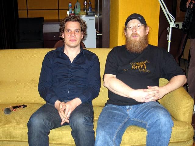 Zwei Männer sitzen auf einem gelben Sofa