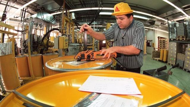 Ein Mitarbeiter der Sika AG beim Verpacken verschiedener Baustoffe.