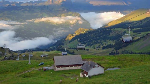 Berglandschaft mit untergehender Sonne und einem Sessellift im Vordergrund.