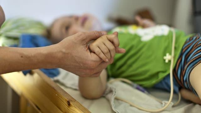 Frau hält Hand von krankem Kind