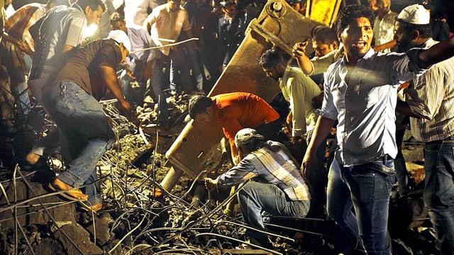 Menschen suchen verzweifelt in den Trümmern des Gebäudes in Mumbai nach weiteren Opfern.