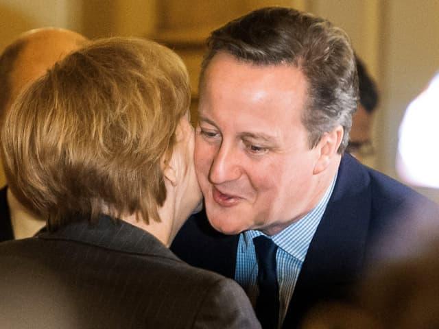 Premier Cameron (rechts) und die deutsche Kanzlerin Merkel (links) geben sich ein Wangenküsschen.