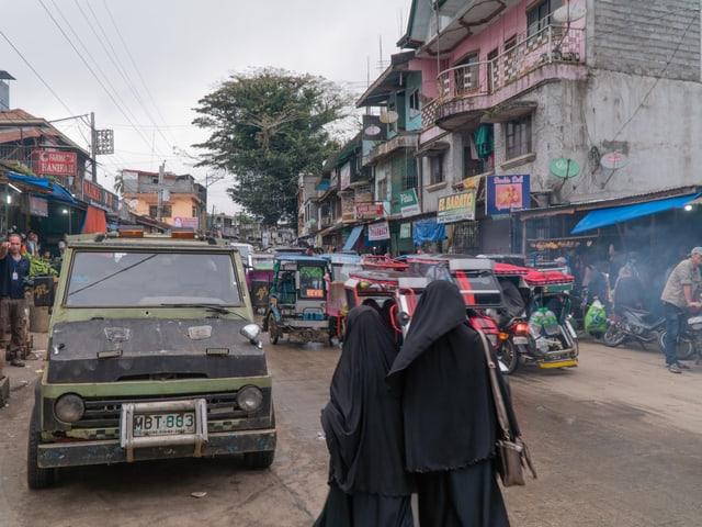 Zwei verhüllte Frauen überqueren eine belebte Strasse