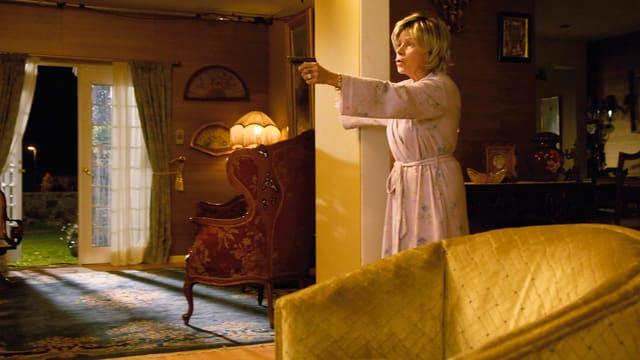 Eine ältere Dame im Bademantel hält eine Pistole in der Hand. Sie steht in ihrer Wohnstube.