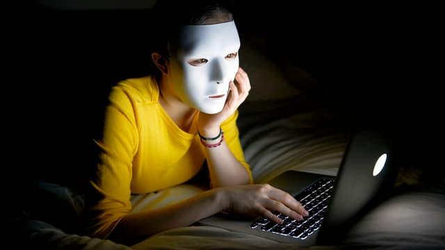 Eine Frau mit weisser Maske sitzt vor dem Laptop.