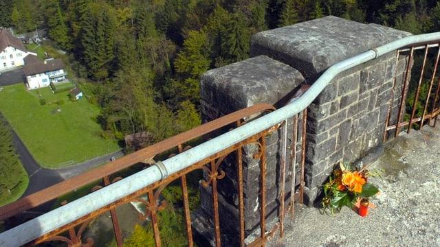 Blumen erinnern an einen Menschen, der von dieser Brücke in den Tod gesprungen ist.