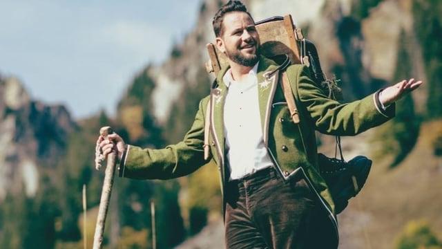 Junger, bärtiger Mann mit Wanderstab vor Bergkulisse.