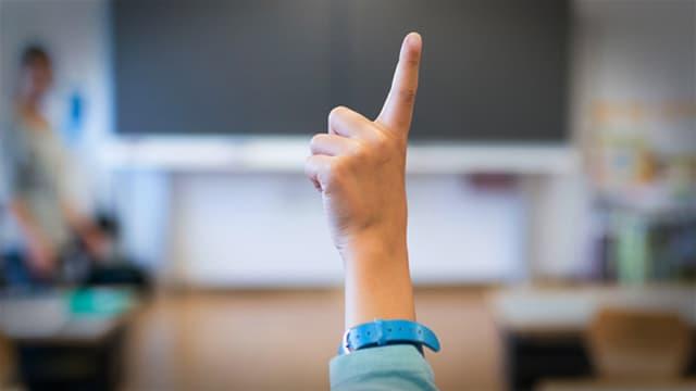 Schüler streckt in der Klasse die Hand auf. Lehrerin im Hintergrund.
