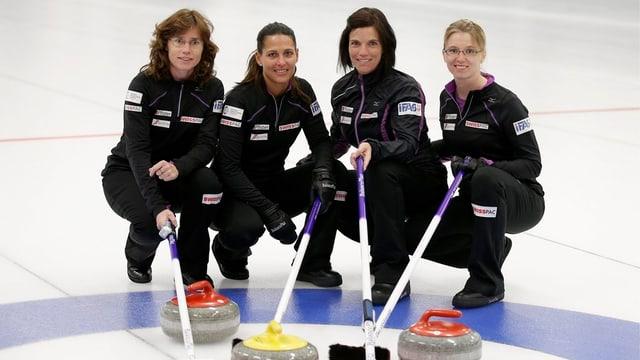Das Curling-Team posiert mit Steinen und Besen auf dem Eis.