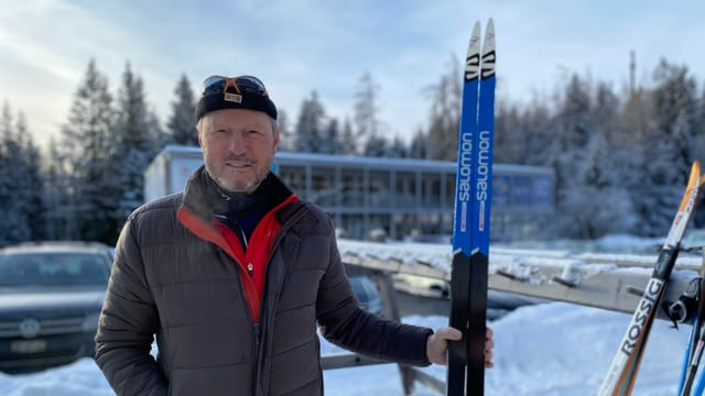 Ernst Orlik, scolast da passlung a Lai, cun in pèr skis da passlung en maun.