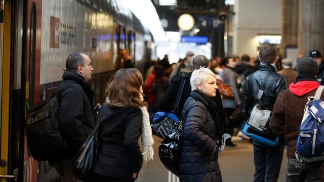 Menschen steigen aus einem Zug aus.