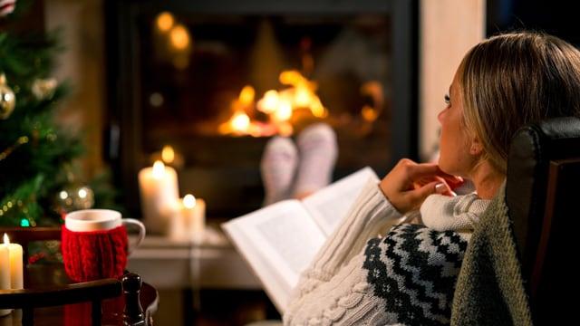 Eine Frau liest ein Buch vor einem Kamin. Im Hintergrund sieht man einen Weihnachtsbaum.