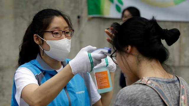 Medizinerin misst Fieber bei einer Frau