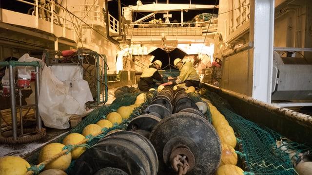 Auf dem Deck eines Schiffs liegt ein grosses Netz, Schwimmer und Ketten.