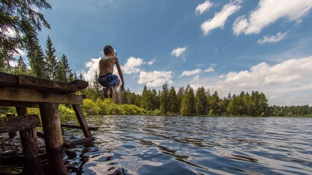 Ein Kind springt ins Wasser.