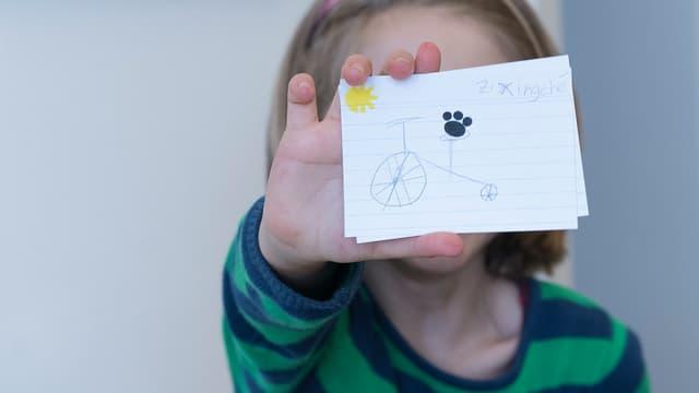 """Ein Mädchen hält eine Karteikarte vors Gesicht. Darauf sind ein gezeichnetes Fahrrad und das Wort """"zixingche"""" zu sehen."""
