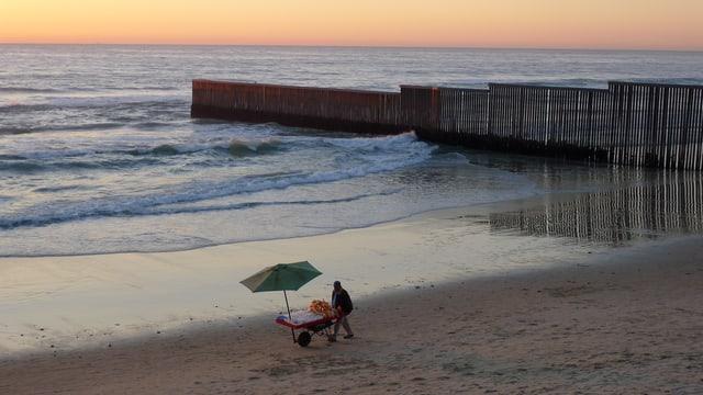 Trennzaun verläuft bis ins Meer bei Abendstimmung.