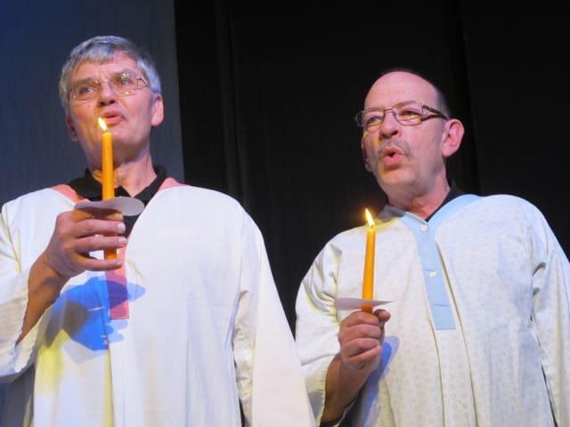 Zwei Sänger mit Kerze im Nachthemd.