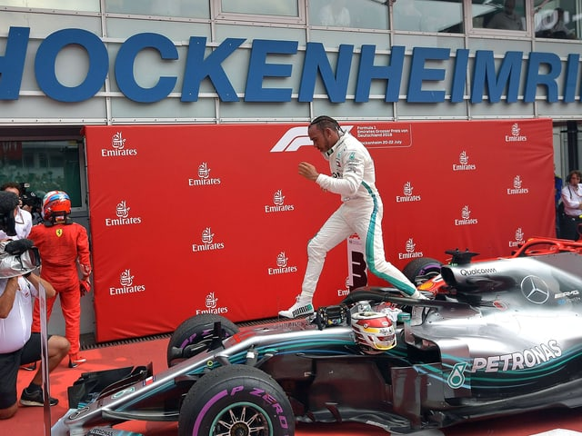 Lewis Hamilton springt von seinem Mercedes.