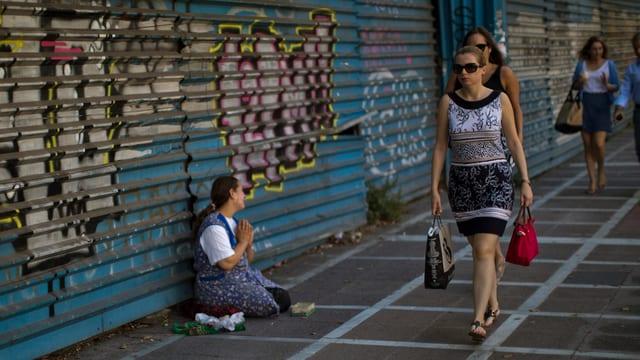 Bettelnde Frau auf der Strasse und Passanten.