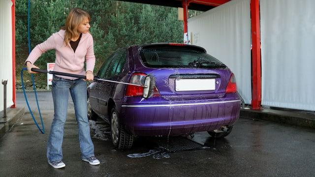 Eine junge Frau wäscht ihr Auto in einer Selbstbedienungsbox