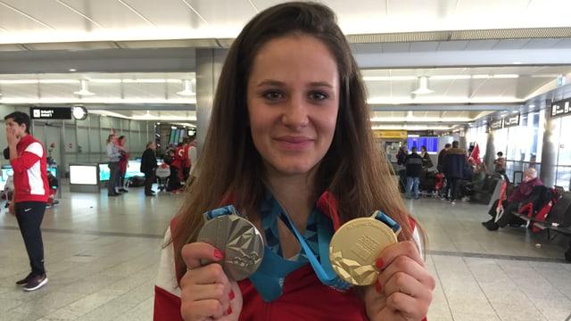 Talina Gantenbein mussa sias duas medaglias (aur ed argient) a la plazza aviatica da Turitg