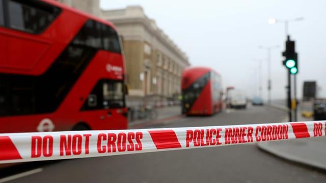 Ein weiss-rotes Absperrband der Polizei, im Hintergrund zwei rote London Busse