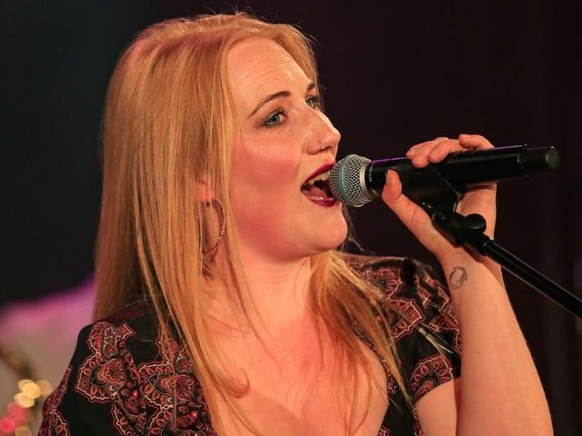 Frau singt in ein Mikrophon.
