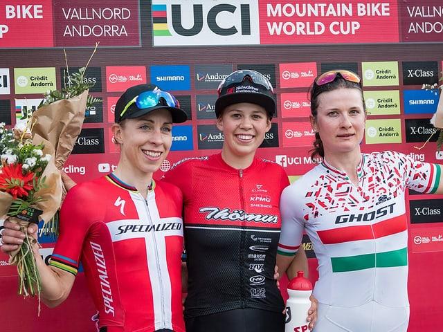 Drei Mountainbikerinnen stehen nebeneinander auf dem Podest.