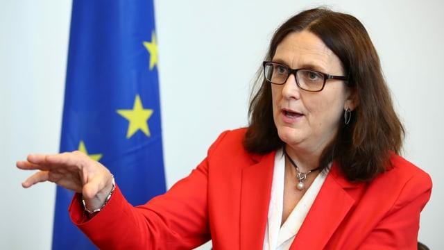 Cecilia Malmström in Genf, im roten Jacket vor der EU-Flagge