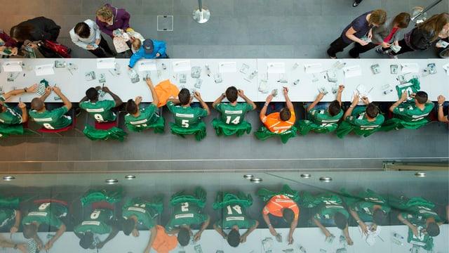 Blick von oben auf einen langen Tisch, an dem die Spieler des FC St. Gallen Autogramme verteilen.