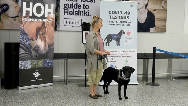 Hund vor einer Plakatwand mit Hundehalterin auf dem Flughafen Helsinki