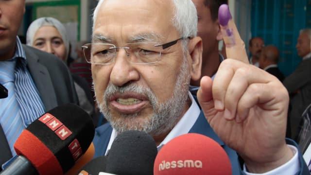 Rached Ghannouchi, zeigt seinen Zeigefinger mit der Stempelfarbe.