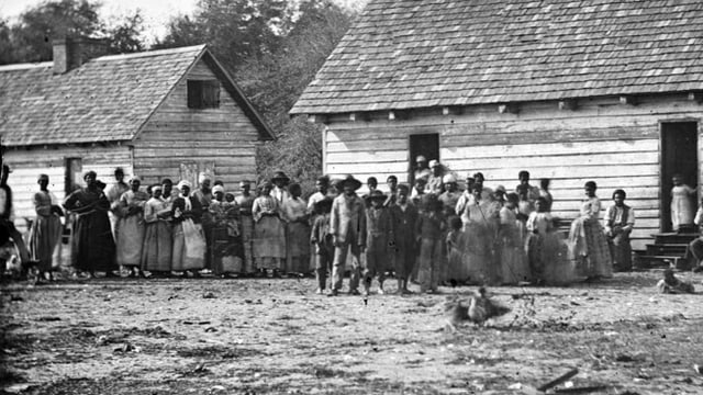 Dutzende Sklaven stehen vor zwei Häusern