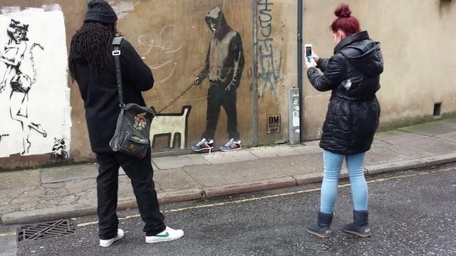 Zwei Menschen stehen vor einem Graffiti mit Turnschuhen.
