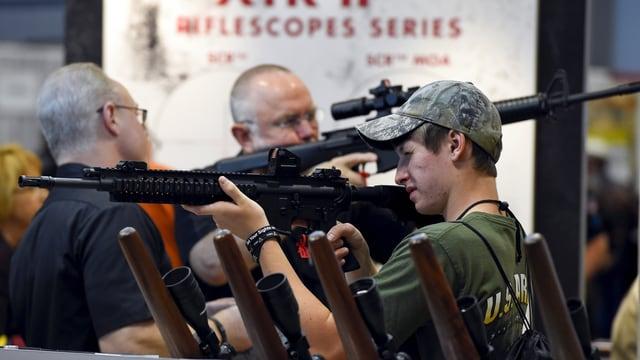 Männer probieren Waffen aus.