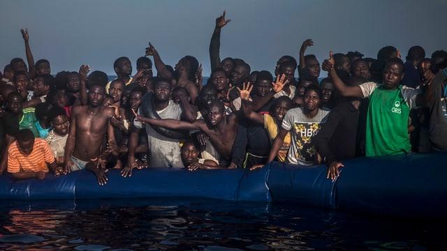 Afrikanische Flüchtlinge dicht gedrängt auf einem Schlauchboot, dem die Luft ausgeht.
