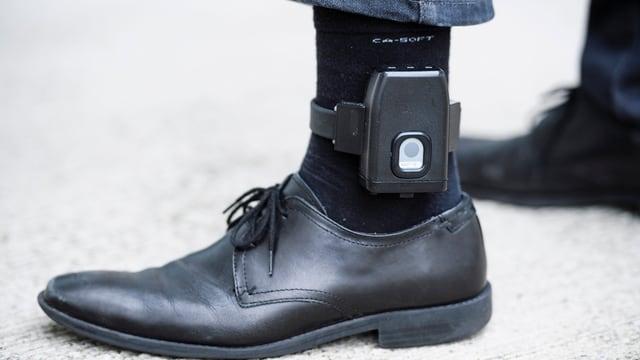 Bein mit einer elektronischen Fussfessel.