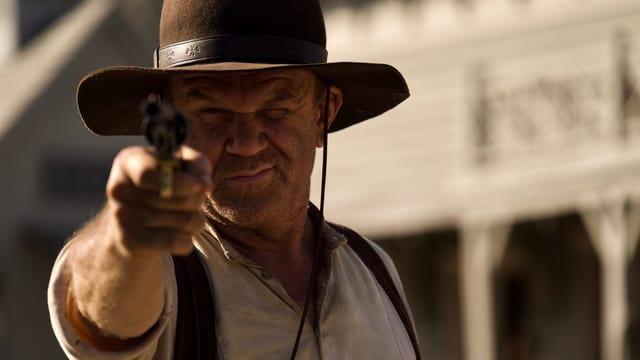 Ein Cowboy zielt mit seinem Revolver direkt auf die Kamera.